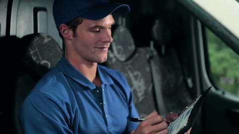 Delivery man in van writing on clipboard Stock Video Footage