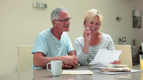 Mature couple opning letter and laughing Stock Video Footage