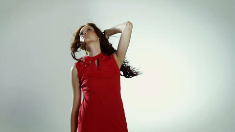 Young woman wearing red dress reaching forwards Stock Video Footage