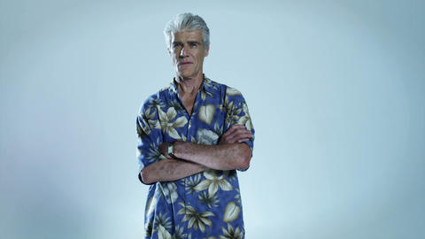 Senior man wearing hawaiian shirt with arms folded Stock Video Footage