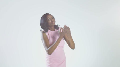 Mature woman wearing pink dress, hands clasped on chest Stock Video Footage