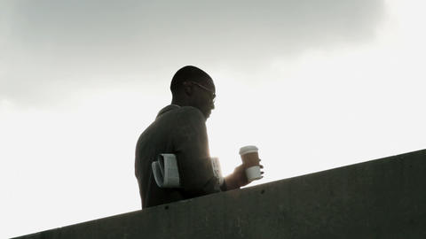 Businessman drinking from disposable cup by wall, low angle Stock Video Footage
