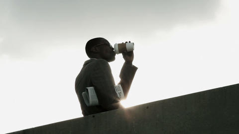 Businessman drinking from disposable cup by wall, low angle Live Action