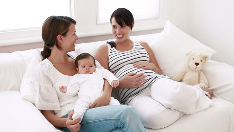 Mother with baby girl and pregnant friend talking, film... Stock Video Footage