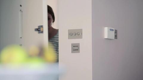 Woman setting burglar alarm and leaving through front door Stock Video Footage