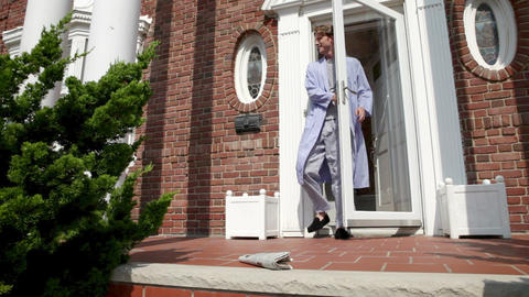 Man wearing pajamas collecting morning newspaper outside... Stock Video Footage