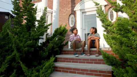 Brother and sister sitting on steps outside house, chatting Stock Video Footage