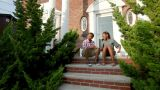 Brother and sister sitting on steps outside house, chatting Footage