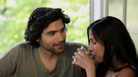 Man pouring juice, tilt up to show couple talking Stock Video Footage
