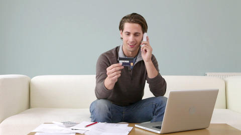 Young man with credit card using laptop Stock Video Footage
