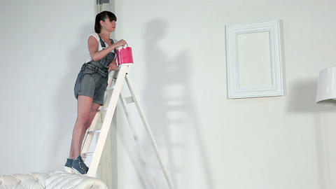 Woman pouring red paint into paint can Stock Video Footage