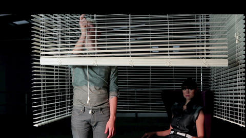 Young couple behind venetian blind Stock Video Footage