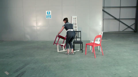 Young woman picking up chairs and placing on floor Stock Video Footage
