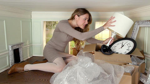 Young woman packing objects and getting angry in small room Stock Video Footage