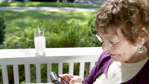Senior woman on porch using smart phone Stock Video Footage