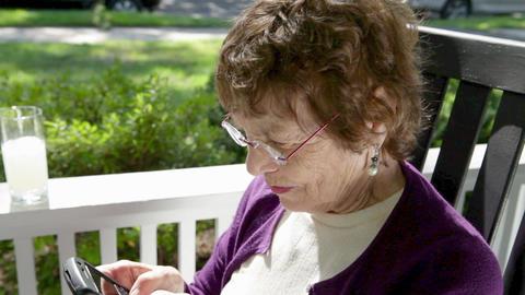 Senior woman on porch using smart phone Stock Video Footage