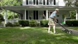 Senior man mowing front lawn Footage