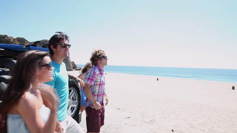 Friends getting out of vehicle at the beach Stock Video Footage