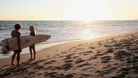 Female and male surfers meeting on the beach at sunset Stock Video Footage