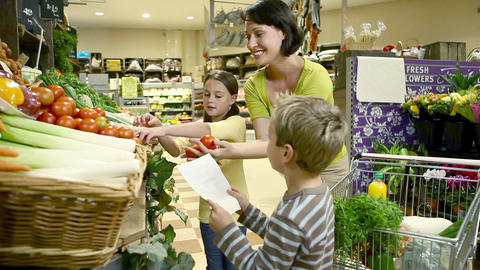 Mother and children getting tomatoes at supermarket Stock Video Footage