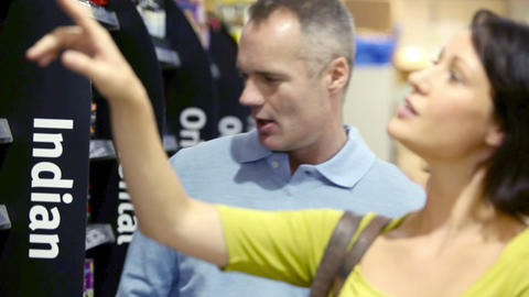 Couple choosing jar of sauce in supermarket Stock Video Footage