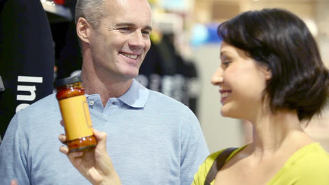 Couple choosing jar of sauce in supermarket Stock Video Footage