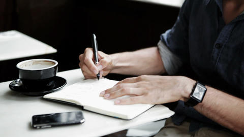 Young man writing in coffee shop Stock Video Footage