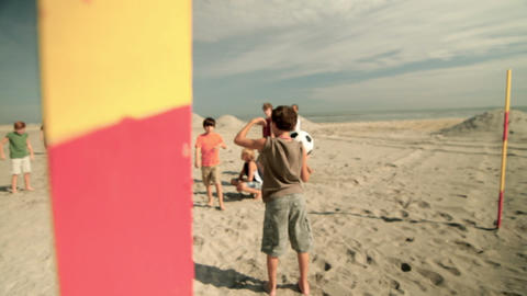 Boys playing with football on beach Stock Video Footage