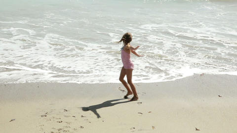 Girl playing at water's edge Stock Video Footage