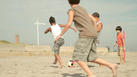 Boys playing football on beach, kick off Stock Video Footage