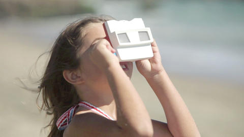 Girl looking through slide viewer on beach Stock Video Footage