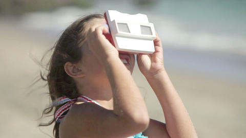 Girl looking through slide viewer on beach Footage