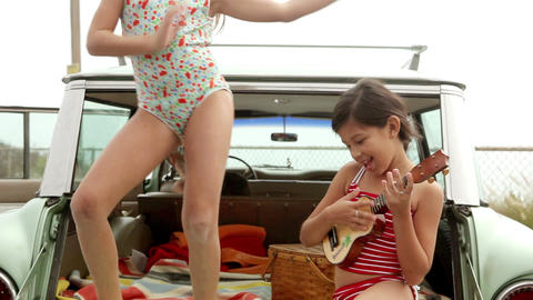 Two girls on car boot, one dancing the other playing guitar Stock Video Footage