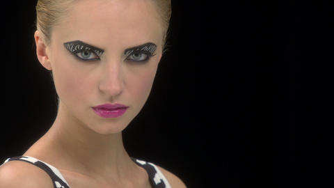 Young woman with zebra stripe eye makeup opening eyes and looking at camera Footage