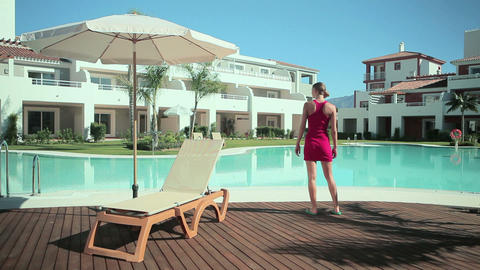 Woman walking on decking by poolside Stock Video Footage