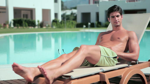 Man removing sunglasses on sunlounger Stock Video Footage