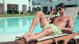 Man removing sunglasses on sunlounger Footage