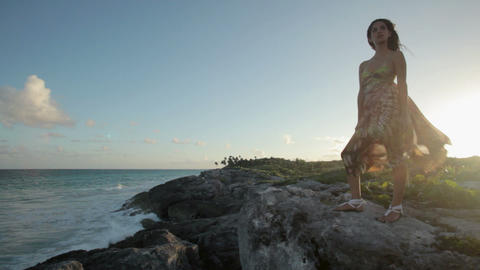 Young woman standing on rocks by the sea with breeze... Stock Video Footage