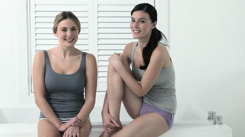 Two young woman sitting on edge of bathtub Stock Video Footage