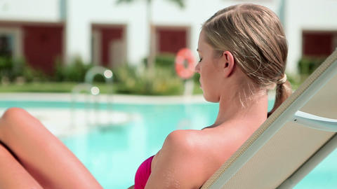 Woman sunbathing on sunlounger at poolside Stock Video Footage