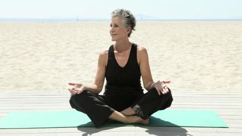 Senior woman doing yoga on beach Stock Video Footage