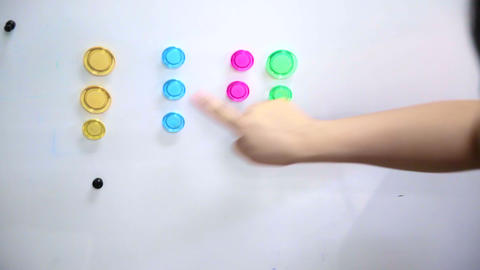 hand categorises colourful magnet on magnetic board Footage