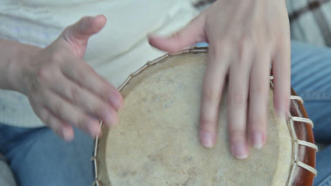 Women playing on Jambe Drum on nature Footage