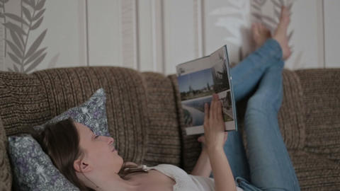 Young woman reading a book on the couch Footage