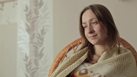 Young woman covered with blanket holding remote control and watching tv at home Footage