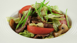 warm salad with veal and roasted mushrooms in white plate Footage