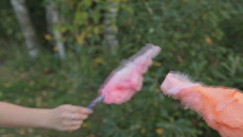 Young couple have fun, fight with cotton candy Footage