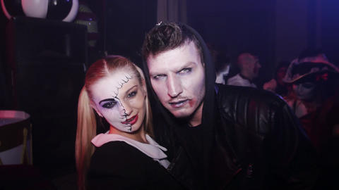 Vamp boy and girl with half painted face show tongue in cam at Halloween party Live Action
