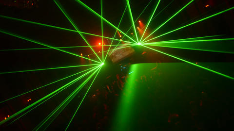 Green sparlking beams from laser show in crowded nightclub. Camera moves Footage