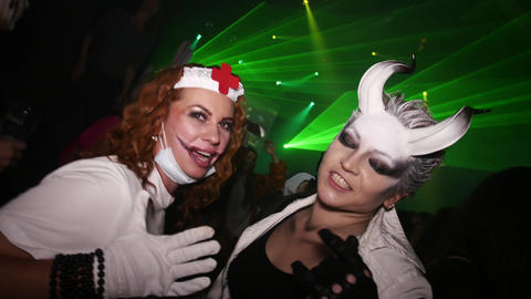 Two woman at Halloween party in club. Nurse, woman with white horns on forehead Footage